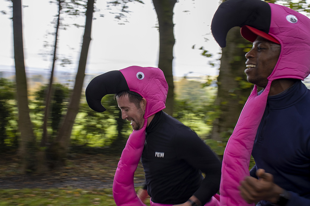 Close up of men smiling and running in flamingo costumes