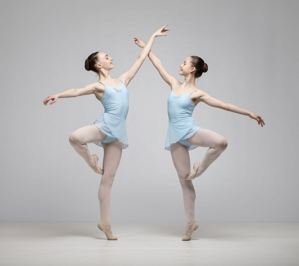 Two ballet dancers in blue posing together