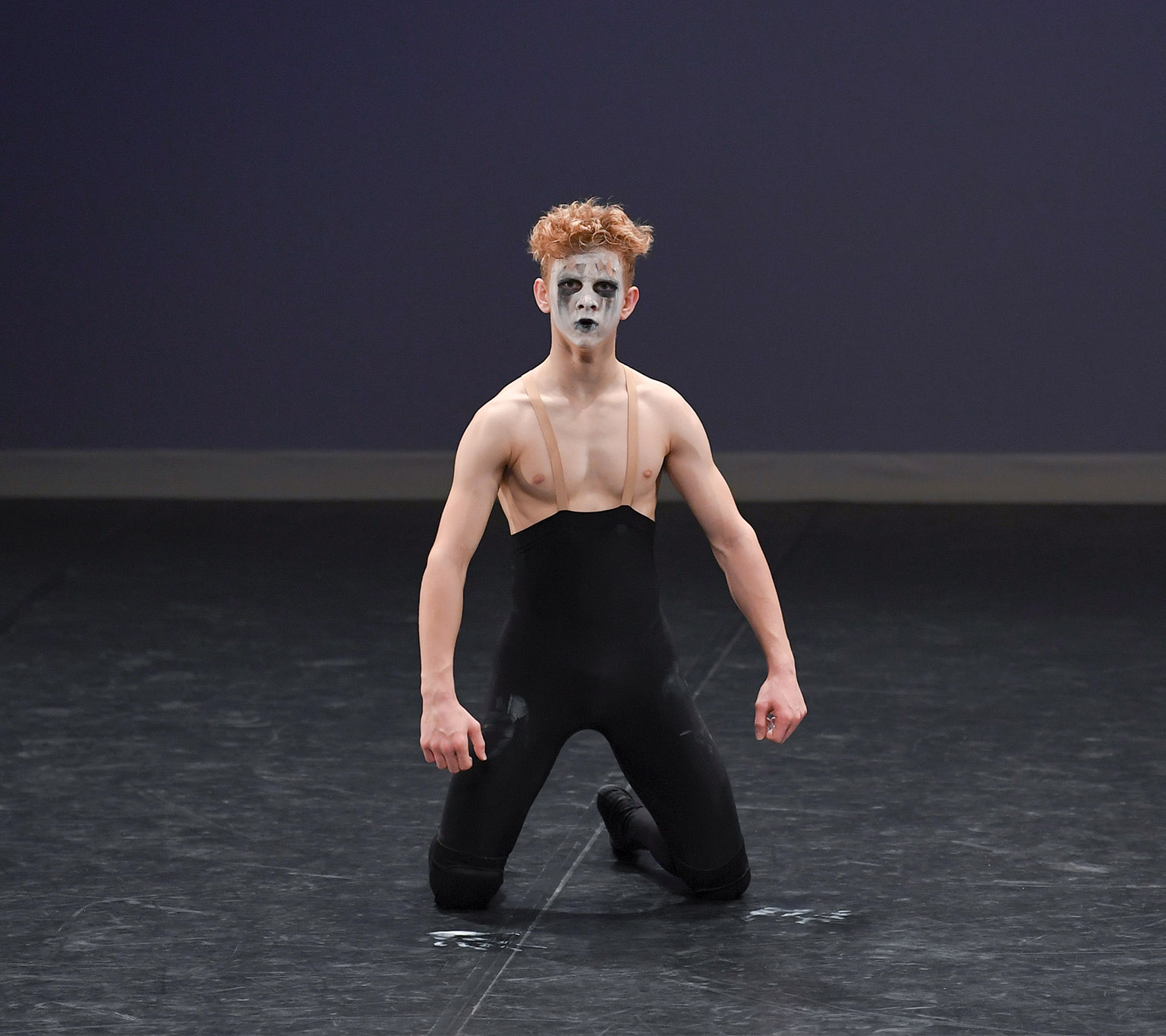 Ballet dancer performing with black and white face paint