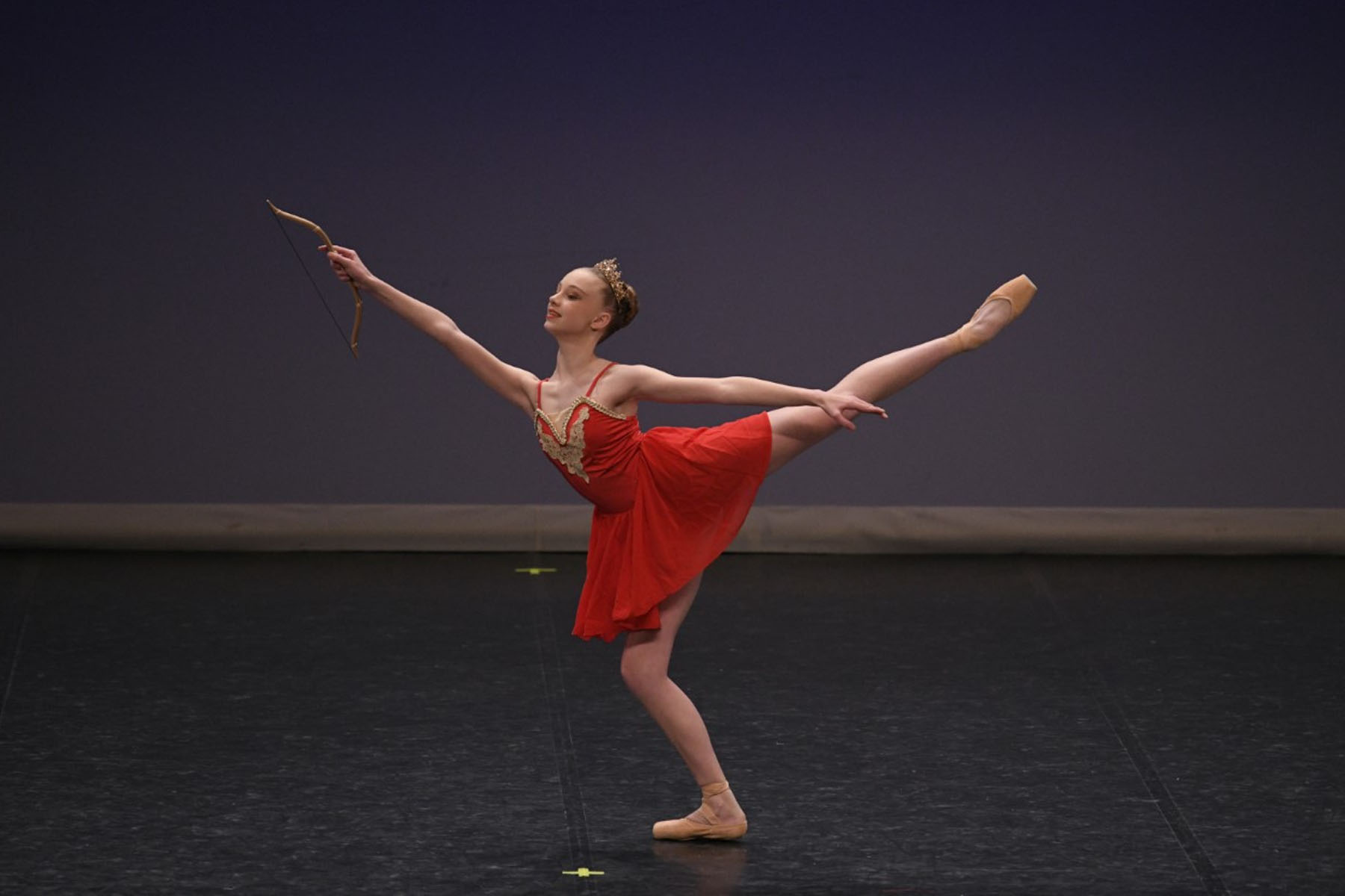 Ballet dancer performing on stage holding a bow