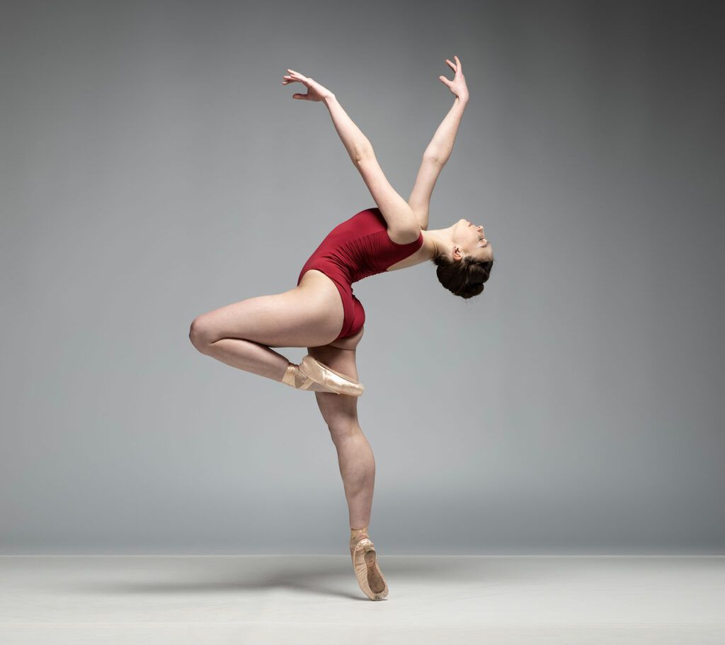 Ballet dancer in red leotard leaning back and balancing on one foot