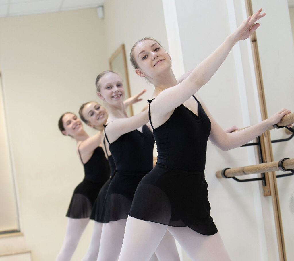 ballet students smiling while stretching