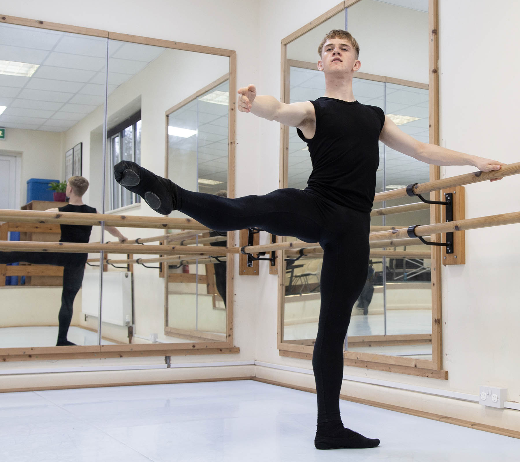 Ballet student holding a pose in studio