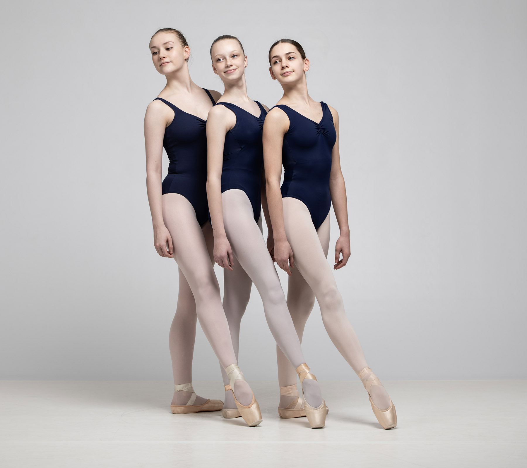 Three ballet students pointing their feet
